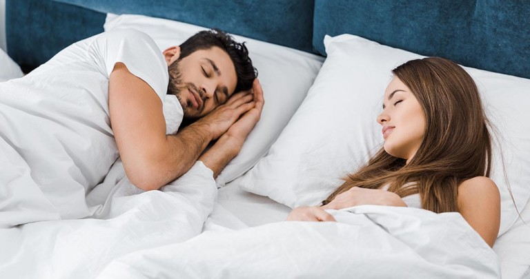 attractive young couple sleeping together in morning