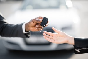 Car salesman handing over keys for new car to young woman against luxury auto