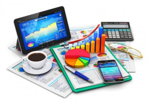 Creative abstract mobile office, stock exchange market trading, statistics accounting, financial development and banking business concept: modern tablet computer PC and black glossy touchscreen smartphone or mobile phone with stock market application software, growth bar chart and pie diagram, ballpoint pen, electronic calculator, golden eyeglasses, report documents and cup of fresh hot coffee drink isolated on white background