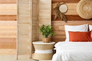 Houseplant on bedside table and folding screen near wooden wall in bedroom