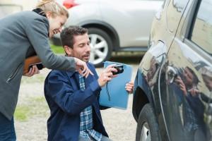 mechanic taking a photo of damage to car